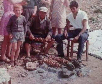 Zak's great uncle cooking souvla using wooden skewers over a stone wall pit turned by hand in the Cyprus village of Eptakomi in 1965